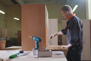 Carpenter working with an electric industrial stapler on the factory, fixing furniture details