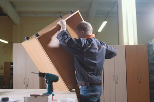 Carpenter working with an electric screwdriver on the workbench on the factory, fixing furniture details
