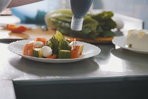 Chef serves greek salad on the plate in restaurant