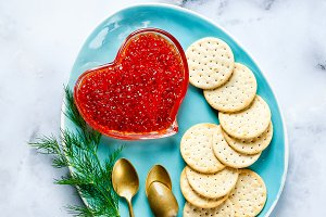 a saucer with red caviar and a crack