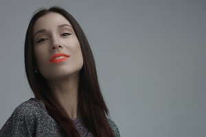 closeup of spanish woman with vivid orange matte lipstick in studio
