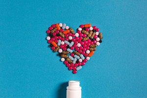 heart shaped of white pills on blue