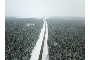 Winter road aerial view surrounded by snowy trees