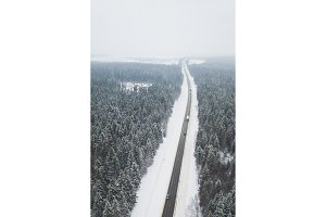 Winter road birds view surrounded by snowy trees - Winter drone photo