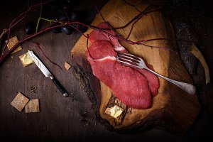 Raw meat on dark wooden board