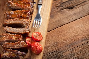 Pork ribs in barbecue sauce and honey roasted tomatoes on a wooden board. A great snack to beer on a rustic wooden table. Top view with copy space