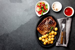 Grilled beef steak served on cast iron plate with tomato salad and potatoes balls. Barbecue, bbq meat beef tenderloin. Top view, slate background