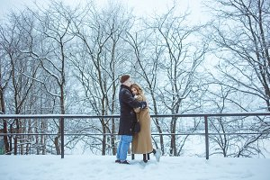 Couple embracing together during winter holidays vacation outside in snow park. Young lovers in classical winter clothes among trees