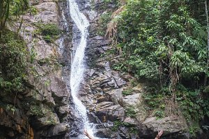 Cheerful couple enjoying river bath by waterfall