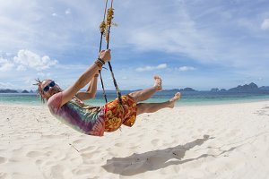 Businessman swinging at tropical beach