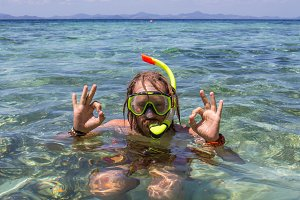 Young man snorkeling in clear shallow tropical sea