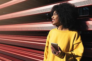 Beautiful afro woman using mobile.
