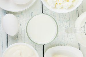 Different dairy products, white wooden background