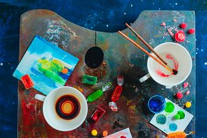 Artist workplace with empty coffee cups, oil and watercolor paint brushes on a colorful palette, sketches and snacks. Flat lay with copy space. Creative occupation concept.