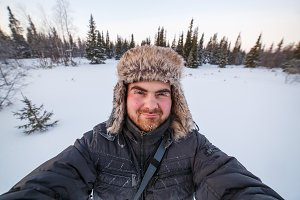 Close-up portrait of middle aged man adventurer with frosted beard in forest or tundra during winter expedition