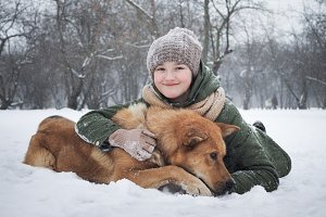 The girl lying in the snow with a huge dog