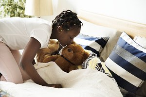 Young teen girl kissing a teddy bear