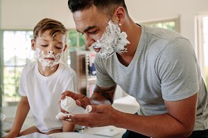 Father and son applying shaving foam