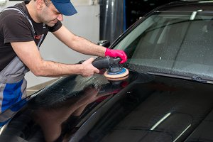A man polishes a black car