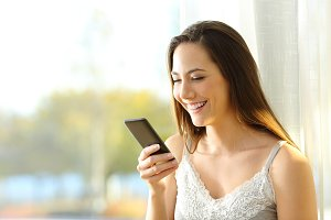 Happy woman reading a smart phone