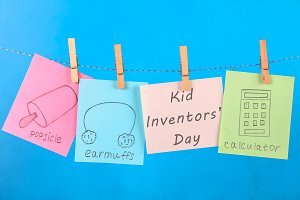 Notes hang on clothes pegs with drawings of children's inventions - popsikl, Earmuffs, calculator on a blue background. Text - Kid Inventors' Day.