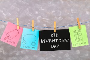 Notes hang on clothes pegs with drawings of children's inventions - popsikl, Earmuffs, calculator on a gray background. Text - Kid Inventors' Day.