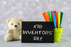 Teddy bear, markers, plaque and drawings of children's inventions - popsicles, Earmuffs, calculator on a gray background. Text - Kid Inventors' Day.