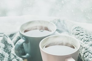 Valentine's day concept - two cups of tea in front of snow background