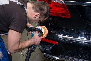 A man polishes a black car
