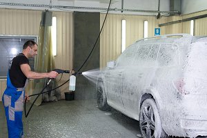 A man washes a black car