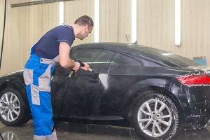 A man washes a black car