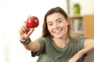 Happy teenager showing an apple