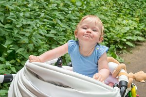 the child sits in the stroller and smiling sweetly