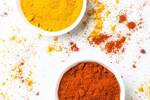 Ground pepper and turmeric on white