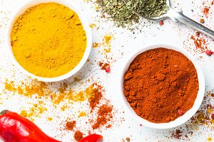 Ground pepper, turmeric and fresh chili pepper on white