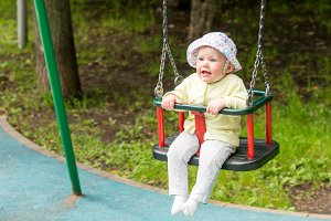 The baby is swinging on the swing