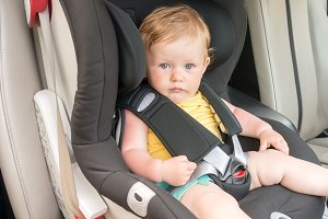 Portrait of pretty toddler boy sitting in car seat. Child transportation safety
