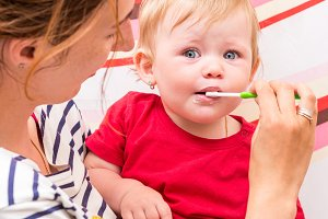 Mother teaching baby girl teeth brushing.