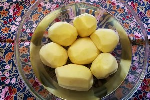 Peeled potatoes in a bowl with water