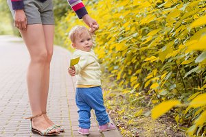 A baby boy walks with mom