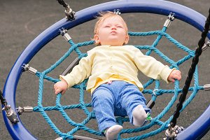 The baby is riding on a swing