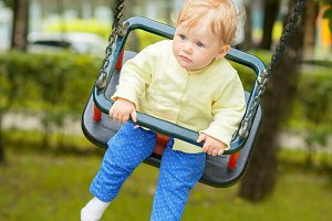 A cute baby child having fun on a swing