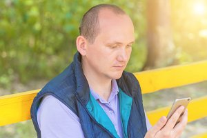 A man sits in a park and looks into the phone