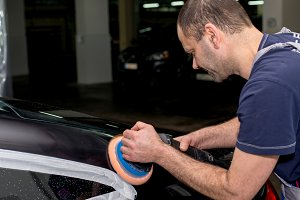 A man polishes a black car with a polisher