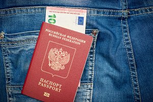 Passport with money in a pocket of blue jeans