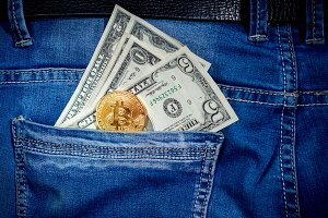 Bitcoin with money in a pocket of blue jeans