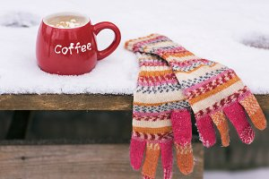 mittens and a red cup with coffee