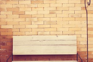 Outdoor wooden chair on brick wall