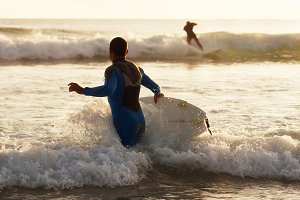 surfer going into the sea at sunset