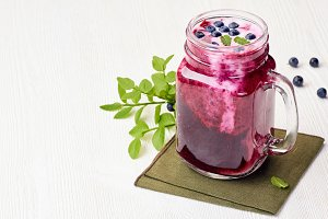 Jar of blueberry smoothie with berries and green leaves